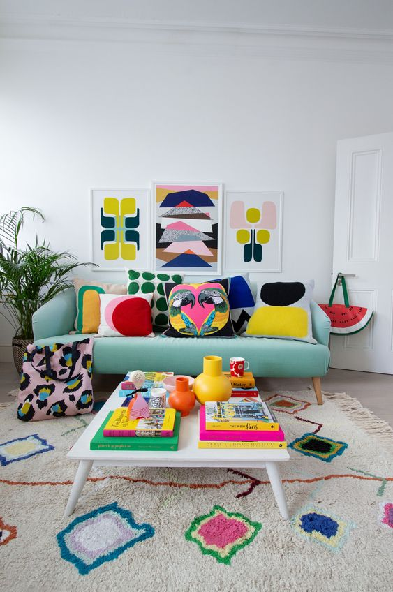 a bright living room with colorful pillows, artworks, a rug and books - all the colors are brought with accessories