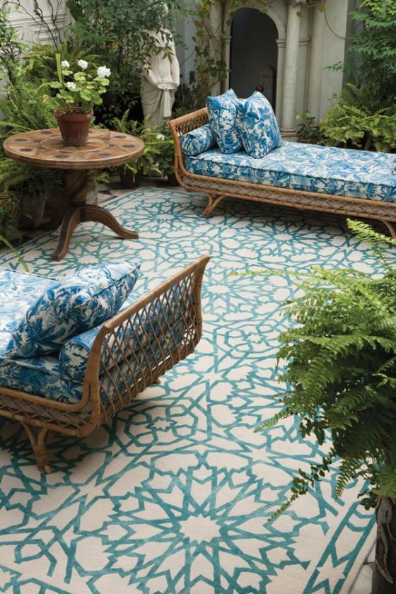 a couple of elegant rattan daybeds dressed up with blue and white printed bedding that matches the mosaic floor