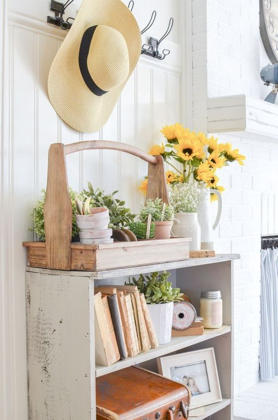a farmhouse cabinet instead of a console, a tool box with platers and a floral arrangement in a vintage pitcher