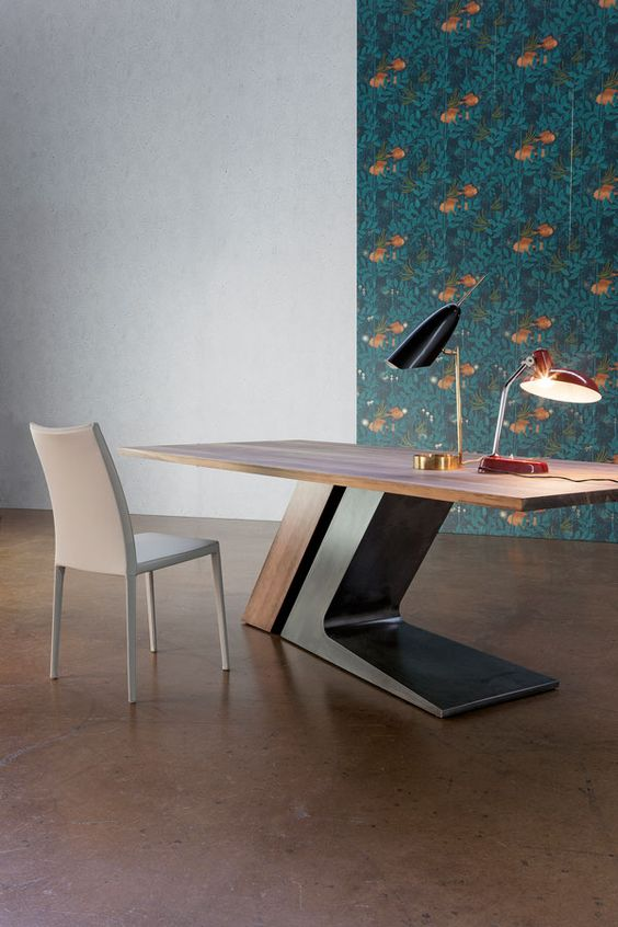 a large sculptural desk in rich stain and dark metal features a large comfortable base that makes a statement