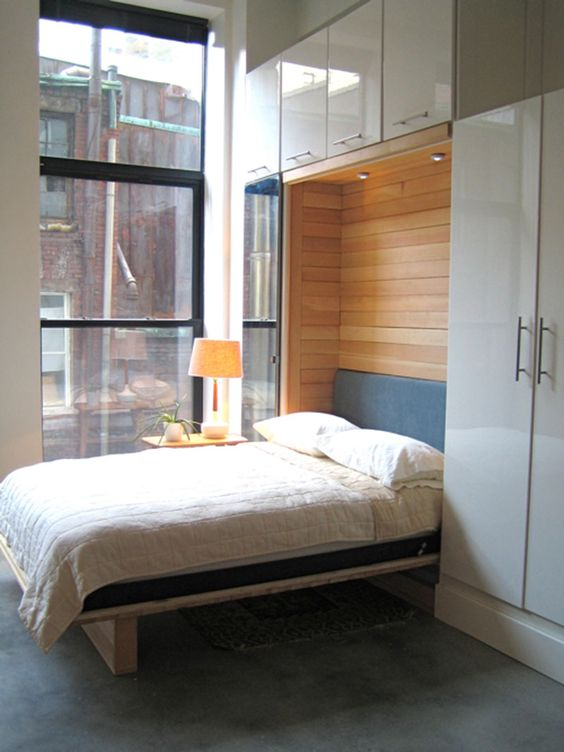a stylish Murphy bed with wood clad inside and sleek storage units on all the sides