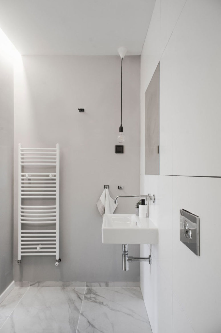 The bathroom is minimalist, with white marble tiles and bulbs plus a wall-mounted sink