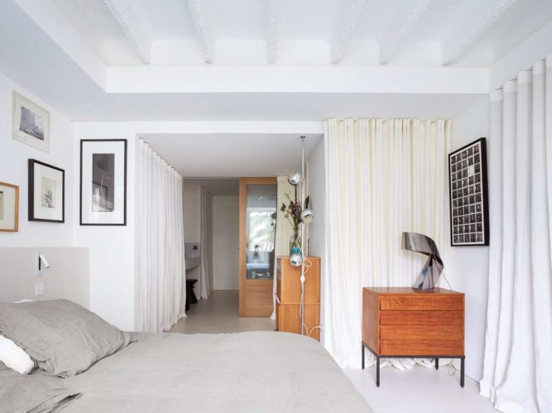 The master bedroom shows off a grey bed, a gallery wall, a stained dresser and more curtains for privacy