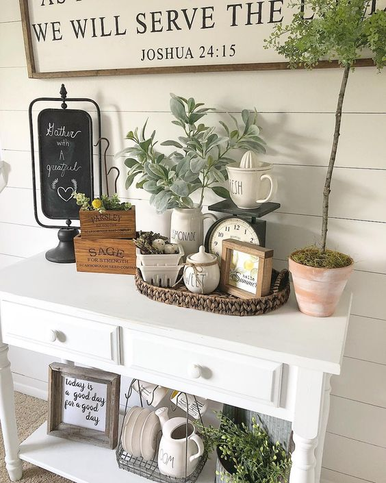 a cozy summer farmhouse entryway with a sign, pale greenery, a basket, some pots and porcelain