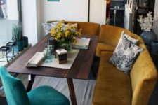 10 a curved mustard bench and a teal chair are paired to create a cozy mid-century modern breakfast nook