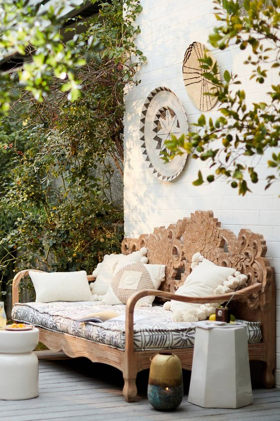 a hand carved wooden daybed with an ornate back is a gorgeous idea for a boho chic outdoor space