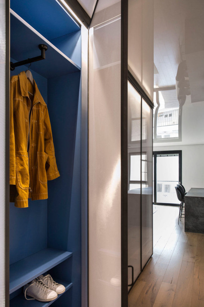 The entryway is done with an open blue storage unit with sliding doors, another its side is in the bedroom