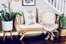 11 a boho summer entryway with a rattan bench, planters with greenery on stands, a straw hat and a boho rug