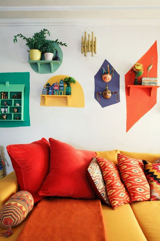 a colorful retro living room with a yellow and red sofa and bright touches on the wall - each shelf is different and highlighted with a different color