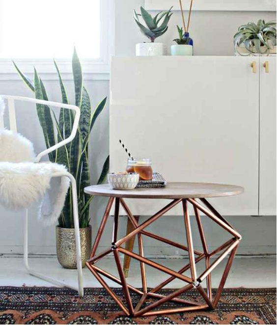a stylish modern coffee table with a geometric copper base and a concrete countertop looks wow