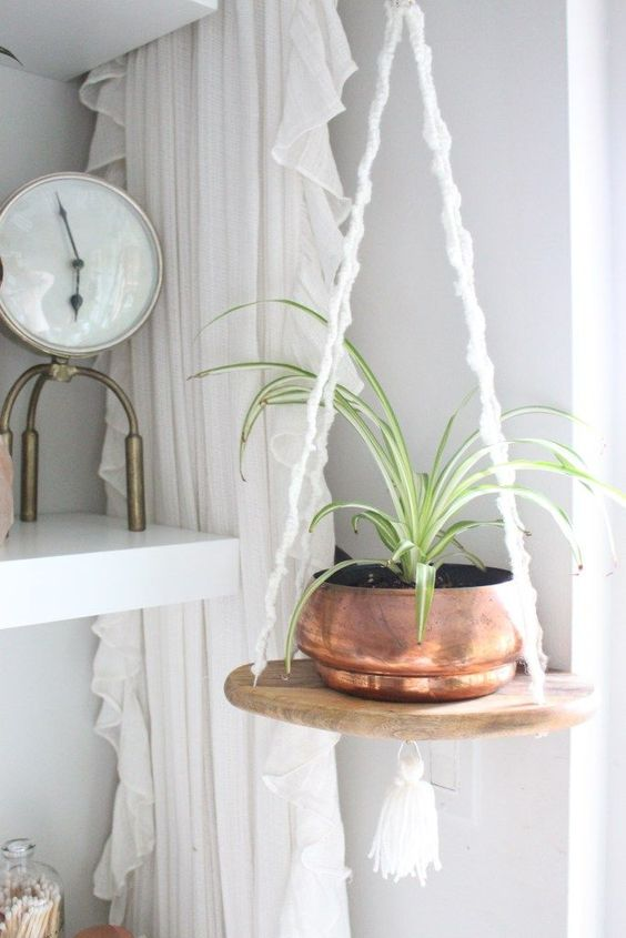 an easy hanging shelf of a cutting board and some macrame cords with a copper planter looks very boho-like