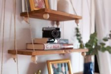 12 a boho hanging shelf composed of several tiers of various sizes, beads on a wooden holder
