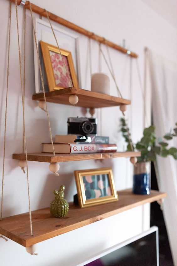a boho hanging shelf composed of several tiers of various sizes, beads on a wooden holder