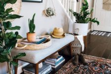 12 a boho summer entryway with potted plants and cacti, a boho rug, a wicker basket and an artwork