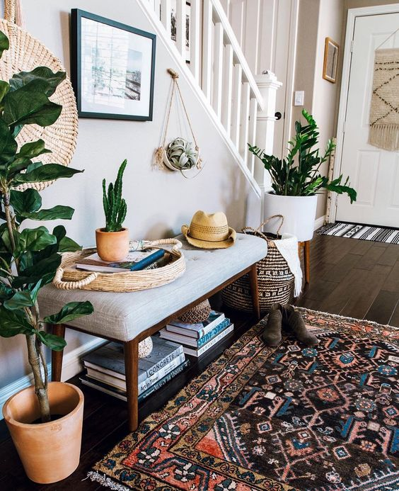 a boho summer entryway with potted plants and cacti, a boho rug, a wicker basket and an artwork