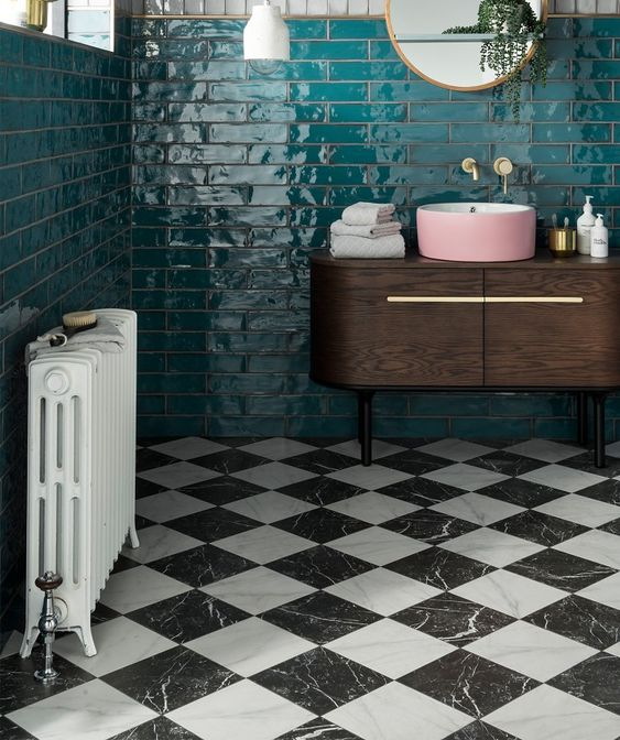 a retro bathroom with emerald tiles on the walls and black and white marble tiles on the floor