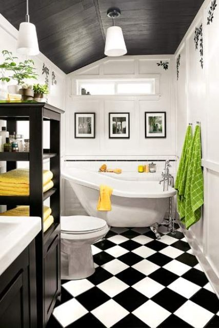 a monochromatic bathroom done with black and white tiles on the floor and spruced up with colorful towels and textiles