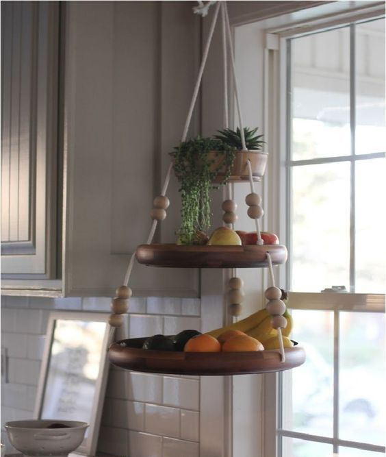 a fun hanging shelf for fruit with beads and ropes and some succulents on top is a cute and easy idea