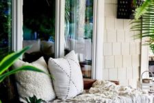 14 a rattan daybed with pillows, blankets and a statement wicker lampshade over it is relaxed tropical-inspired idea