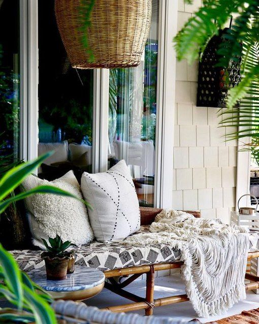 a rattan daybed with pillows, blankets and a statement wicker lampshade over it is relaxed tropical-inspired idea