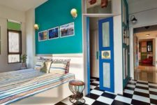 14 a retro bedroom with a black and white tile floor, a teal wall and a bright blue door for more color
