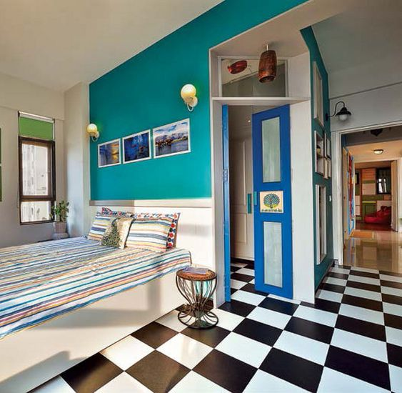 a retro bedroom with a black and white tile floor, a teal wall and a bright blue door for more color