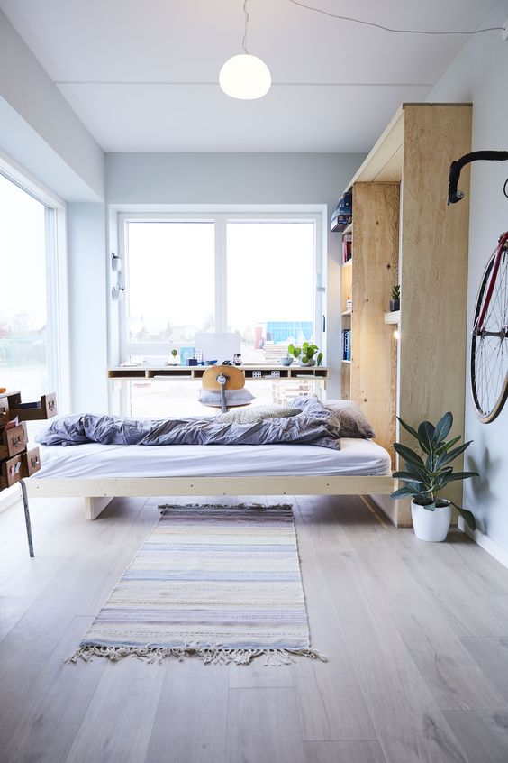 a Nordic light-filled bedroom with a Murphy bed integrated into a storage unit