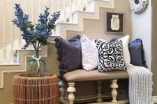 15 a bright farmhouse summer entryway with a floral arrangement, navy and white printed pillows and a rattan table