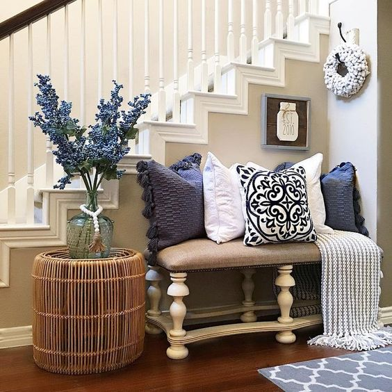 a bright farmhouse summer entryway with a floral arrangement, navy and white printed pillows and a rattan table