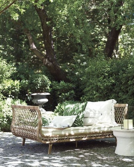 a rattan daybed with tall armrests and lots of pillows invites you to have a nap right here