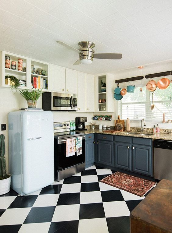 a retro kitchen with a black and white tile floor, colorful pots and pans and a retro-inspired pastel fridge