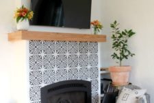 15 mosaic patterned grey and white tiles plus a wooden mantel look amazing and bring elegance to the rustic space