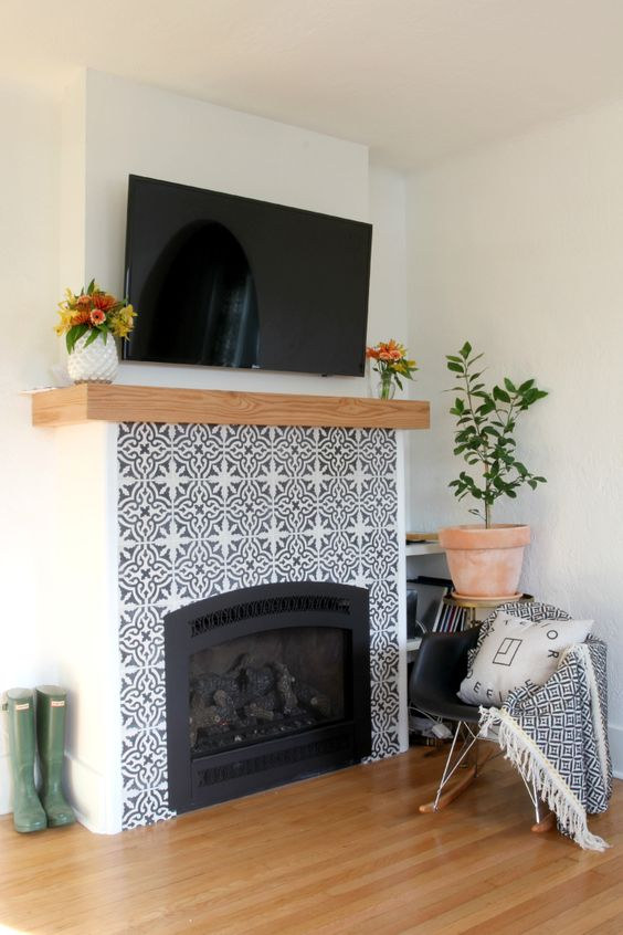 mosaic patterned grey and white tiles plus a wooden mantel look amazing and bring elegance to the rustic space