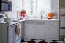 16 a 1950s inspired kitchen with a black and white tile floor and neutral cabinets yet colorful plates and pots