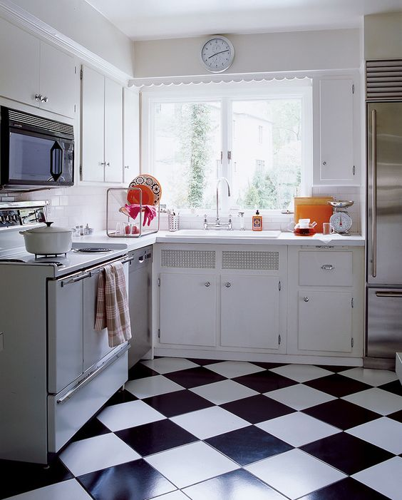 a 1950s inspired kitchen with a black and white tile floor and neutral cabinets yet colorful plates and pots