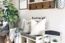 16 a bright summer entryway with potted greenery, a gallery wall in black and white and a chalkboard chair