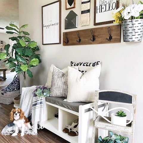 a bright summer entryway with potted greenery, a gallery wall in black and white and a chalkboard chair