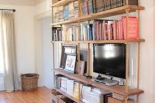 16 a large hanging shelving unit with thick rustic wooden shelves and thick ropes plus baskets under it for more organization