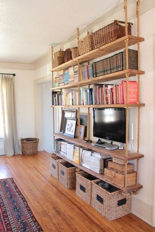 a large hanging shelving unit with thick rustic wooden shelves and thick ropes plus baskets under it for more organization