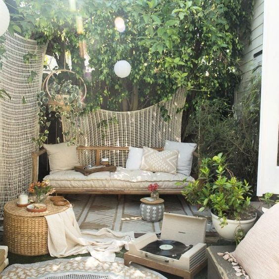 a rattan outdoor daybed under a tree to avoid much sunshine is a perfect fit for a neutral boho zone