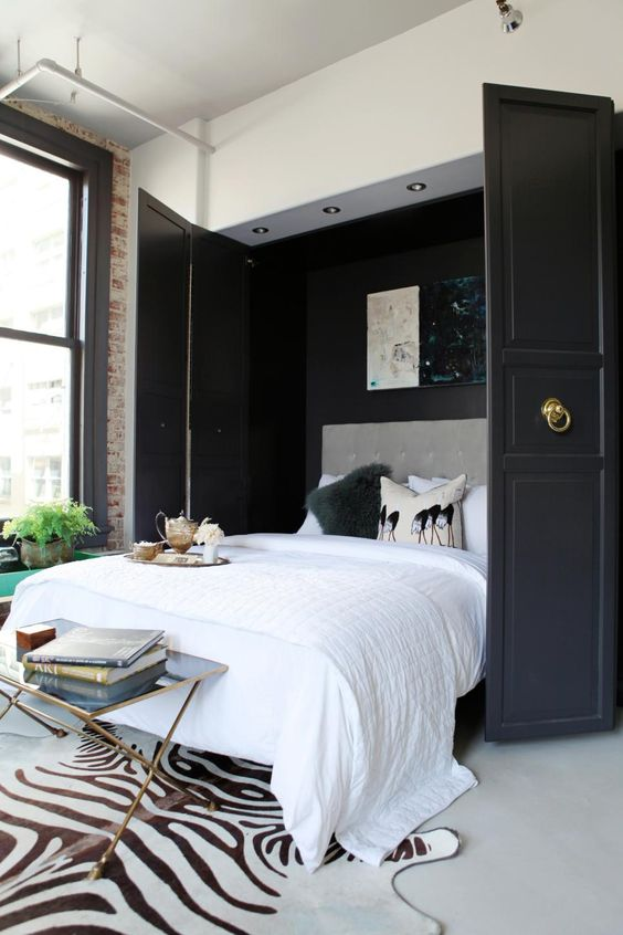 a stylishly hidden Murphy bed with black doors and ring pulls is a gorgeous idea for a refined bedroom