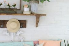 17 a bright vintage-inspired summer entryway with coral blooms in a vase and tubes, coral pillows, a straw hat and a blue bench