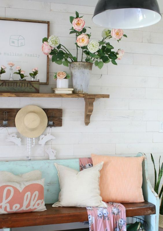 a bright vintage inspired summer entryway with coral blooms in a vase and tubes, coral pillows, a straw hat and a blue bench