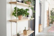 17 a large shelving unit with several tiers and thick ropes is a fresh take on a traditional console table that doesn't take floor space