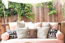 17 a recycled pallet daybed on casters with a pink cushion and an assrtoment of pillows is a veyr inviting furniture idea