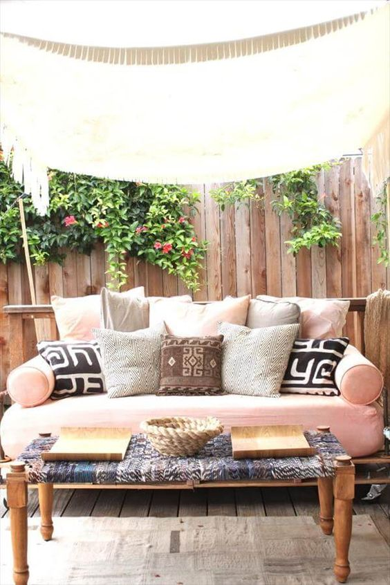 a recycled pallet daybed on casters with a pink cushion and an assrtoment of pillows is a veyr inviting furniture idea