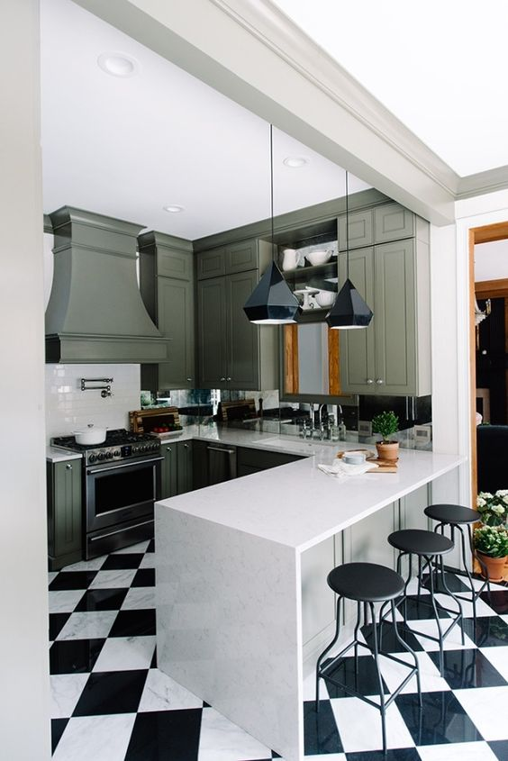 a retro kitchen renovation with green cabinets and a black and white tile floor for a more retro feel