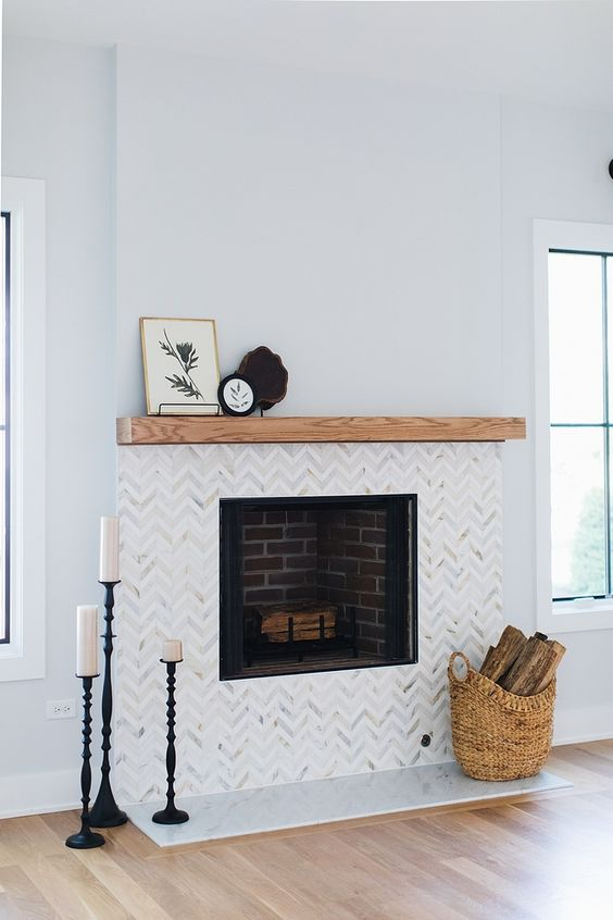 marble chevron clad tiles and a wooden mantel create a chic and stylish look and make the fireplace more elegant