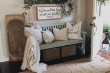 18 a cozy farmhouse summer entryway with a light blue bench, greenery and a greenery wreathh plus wood