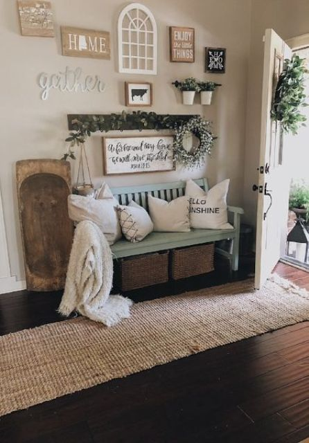a cozy farmhouse summer entryway with a light blue bench, greenery and a greenery wreathh plus wood